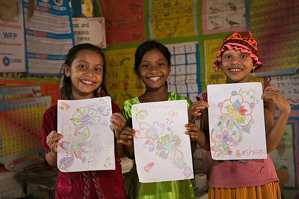 UNICEF-RR-0302 - 0303 Boshara (8) with her best friends Jannatul Ferdous (10) and Jainob Bibi (8) showing drawing with a smiling face. DAM Learning Centre, Block-C, Camp-7.  Photo: b.a.sujaN / UNICEF / Map