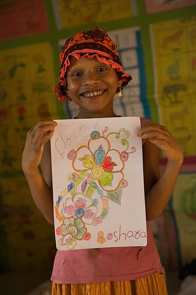 UNICEF-RR-0299 – 0301  Boshara (8) showing her colorful flower drawing. DAM Learning Centre, Block-C, Camp-7.  Photo: b.a.sujaN / UNICEF / Map