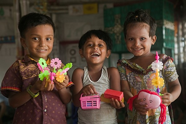 UNICEF-RR-0201-0204  Ohidur Rahman (4), Usmaida (4) and Nur Asia (4) are so much happy to show their colorful play materials inside the  BRAC-UNICEF Multi-Purpose Child and Adolescent Centre.  (joyful playing)   Camp-18, block G-43, Ukhiya, Cox's Bazar Photo: b.a.sujaN / UNICEF / Map