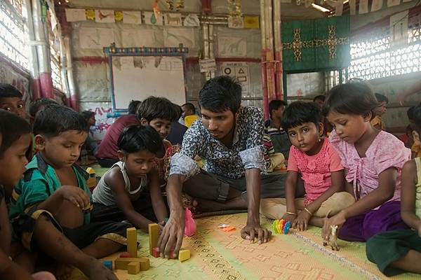 UNICEF-RR-0197-0200  Mahbub (22) a CFS Volunteer demonstrating Rohingya children 'how to play with colorful blocks' inside the  BRAC-UNICEF Multi-Purpose Child and Adolescent Centre.  Camp-18, block G-43, Ukhiya, Cox's Bazar Photo: b.a.sujaN / UNICEF / Map