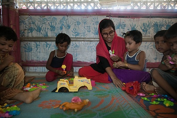 UNICEF-RR-0190-0193  Bulbul Akter (20) working as an Outreach Worker is demonstrating Rohingya children 'how to play with colorful blocks' inside the  BRAC-UNICEF Multi-Purpose Child and Adolescent Centre.  Camp-18, block G-43, Ukhiya, Cox's Bazar Photo: b.a.sujaN / UNICEF / Map