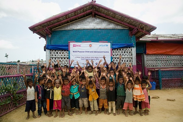 UNICEF-RR-0205-0214  A group of Rohingya children posing for photograph in front of the BRAC-UNICEF Multi-Purpose Child and Adolescent Centre, Camp-18, block G-43, Balukhali 2, Ukhiya, Cox's Bazar supported by Canadian government, KFW (a German Cooperation), The Government of the Republic of Korea, USA.    Camp-18, block G-43, Ukhiya, Cox's Bazar Photo: b.a.sujaN / UNICEF / Map