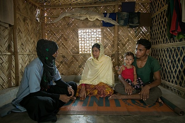 UNICEF-RR-0043-0046  Nur Shamima (20) a well-known community health worker (CHW) from PHD Health Post visiting  Mortoza Bibi (20) and her two children in their house in Kutupalong camp.  Portrait of a happy family should look like the way Mortoza Bibi and Mohammad Amin are living. A better health support could motivate person positively and change their mind-set. Mortoza Bibi (20) wife of Mohammad Amin (26) and mother of two children Unaisa Bibi (18 month) and Maymun Akther (80 days) was struggling to convince her husband initially to take her PHD Health Post for regular check-up. Because he always believes in 'KOBIRAJ' (local doctor without any professional degree). First time she visited PHD health facility with a CHW and later able to accompany with her husband. After continuous home visit for follow-up and vaccination by CHW's changed Amin's mind and now he believes PHD health facility is good for all especially for women and children. Currently, Mortoza Bibi takes birth control pill but her husband wish to have two more children in future.   Kutupalong, UKHIA, Cox's Bazar. Photo: b.a.sujaN / UNICEF / Map