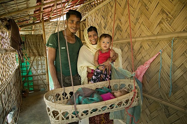UNICEF-RR-0031-0042  Portrait of a happy family should look like the way Mortoza Bibi and Mohammad Amin are living. A better health support could motivate person positively and change their mind-set. Mortoza Bibi (20) wife of Mohammad Amin (26) and mother of two children Unaisa Bibi (18 month) and Maymun Akther (80 days) was struggling to convince her husband initially to take her PHD Health Post for regular check-up. Because he always believes in 'KOBIRAJ' (local doctor without any professional degree). First time she visited PHD health facility with a CHW and later able to accompany with her husband. After continuous home visit for follow-up and vaccination by CHW's changed Amin's mind and now he believes PHD health facility is good for all especially for women and children. Currently, Mortoza Bibi takes birth control pill but her husband wish to have two more children in future.   Kutupalong, UKHIA, Cox's Bazar. Photo: b.a.sujaN / UNICEF / Map