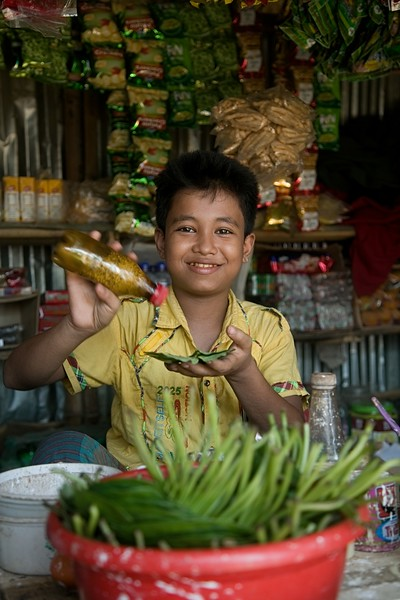 """UNICEF-RR-0215 -0223  MD Jia (12) is preparing betel leaf for his customer in his shop.   MD JIA, 12 """"I want education. I want to study in high school so that one day I could be a doctor. This is my one and only dream. But I don't know how to fulfill it. I am over qualified for BRAC learning centre and they referred me to another school which is yet to establish. I along with my mother and six siblings fled from Myanmar and lost our father on the way in hill. I am running a small shop to earn some money. and to set up the shop my mother was forced to vend her ear rings. Due to my mother's age limit we didn't receive any LPG and we collect relief cloths, plastics and branch of tree from different camps to use as fuel to cook food regularly. My younger sister was seriously ill due to plastic smoke during cooking. We are living a miserable life here. We are refugee here and I don't want to keep this status anymore. I definitely want to go back my country one day"""".  Address in Myanmar: 100, Akyab, Buthidoung, Myanmar.  Camp Address: H - 0626, Block A-7, Camp 16, Shofiullah Kata,  Ukhiya, Cox's Bazar.  Photo: b.a.sujaN / UNICEF / Map"""