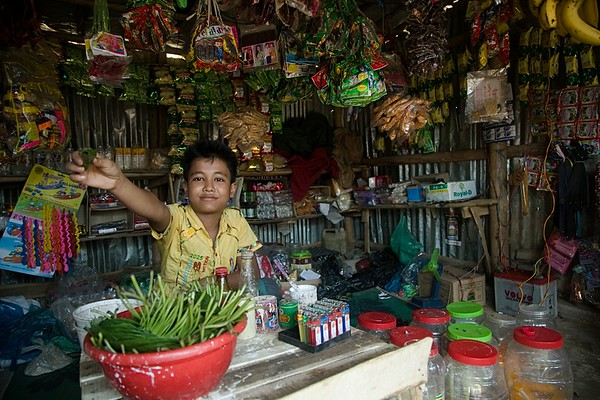 "UNICEF-RR-0215 -0223  MD Jia (12) is preparing betel leaf for his customer in his shop.   MD JIA, 12 ""I want education. I want to study in high school so that one day I could be a doctor. This is my one and only dream. But I don't know how to fulfill it. I am over qualified for BRAC learning centre and they referred me to another school which is yet to establish. I along with my mother and six siblings fled from Myanmar and lost our father on the way in hill. I am running a small shop to earn some money. and to set up the shop my mother was forced to vend her ear rings. Due to my mother's age limit we didn't receive any LPG and we collect relief cloths, plastics and branch of tree from different camps to use as fuel to cook food regularly. My younger sister was seriously ill due to plastic smoke during cooking. We are living a miserable life here. We are refugee here and I don't want to keep this status anymore. I definitely want to go back my country one day"".  Address in Myanmar: 100, Akyab, Buthidoung, Myanmar.  Camp Address: H - 0626, Block A-7, Camp 16, Shofiullah Kata,  Ukhiya, Cox's Bazar.  Photo: b.a.sujaN / UNICEF / Map"