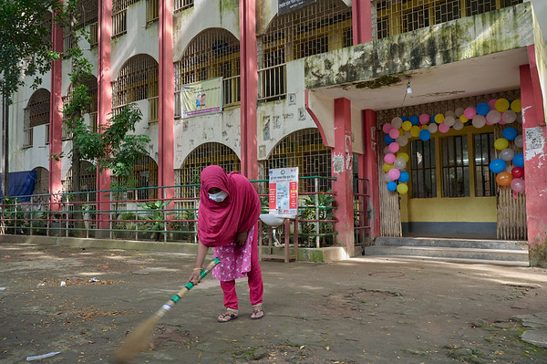 0008-UNICEF-SchoolReopen-COVID-12-09-2021 One of the school's caretaker dusting the schoolyard ahead of the arrival of students. Gandaria Mohila Shomity Government Primary School. Dhaka. Bangladesh. Photo: UNICEF / Sujan / Map