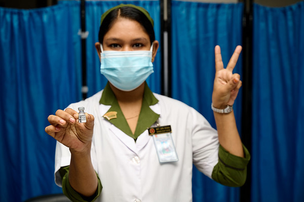 0005-0009-COVAX-21-07-2021-UNICEF A trained vaccinator poses with a victory sign as they are about to vaccinate people with COVAX vaccines in Bangladesh on the launching day on Monday, 21 June 2021. Kurmitola General Hospital, Dhaka, Bangladesh. Photo: UNICEF / B.A.sujaN /Map