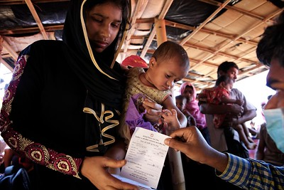 0021-0022-UNICEF-sujaN-Map-21-12-2017  Checking EPI Vaccination Card.  Rohingya refugee children, between 6 weeks and 6 years of age, are provided diphtheria vaccines from 12 UNICEF-supported immunisation points at Bormapara, Cox's Bazar district, Bangladesh.  Photo: UNICEF/b.a.sujaN/ Map