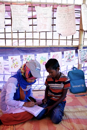 0120-0127  Samira Akter, a Bangladeshi teacher, helps refugee students at a UNICEF-supported learning centre at the Balukhali makeshift settlement for Rohingya in Ukhia, Cox's Bazar, Bangladesh.      Photo: UNICEF / b.a.sujaN/Map