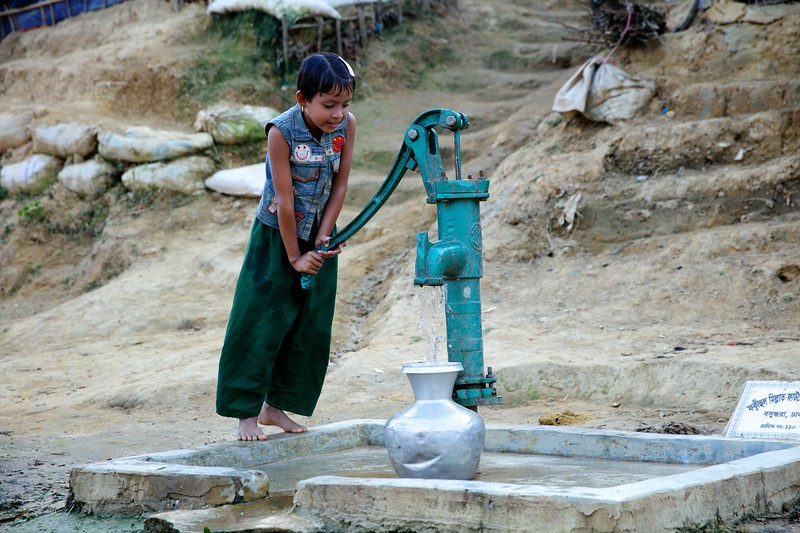 03459-0351 Rafika Begum-(8) She is filling water pot / KOLSHI from hand pump. Rafika is a grade-one student at a UNICEF- supported school. Her mother is unable to go out to collect water from downhill due to health reason. So Rafika has a daily shore to bring water wells to their home at uphill part of a Rohingya refugee makeshift settlement in Ukhiya. She also helps her mother in cooking.  Father Nazir Hossain (57), Rafika is the only daughter and 4 sons. One son is working at BRAC as a volunteer. Photo: UNICEF/b.a.sujaN/Map