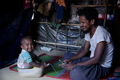 0358-0359 Saber Ahmed (28), husband of Sadekunnahar (26) playing with his 18th month old daughter Mobashera Bibi in side home. Sometimes he keeps busy playing with daughters when Sadekunnahar is busy with her swing machine.  Sadekunnahar is a mother of two children under the age of five. She used to support her husband by earning daily at her home in Myanmar by sewing clothes for women and girls. Military attack on her village forced her to flee to Bangladesh. Recently she bought a sewing machine with the money she borrowed from her neighbours at Rohingya refugee makeshift settlement in Burmapara.  She wants to utilize her skills to earn money for her children. Sadekunnahar and her husband need access to family planning. They have no idea about it since they never had access to the services in Myanmar. Although they have two young children, Sadekunnahar is pregnant again. They are planning to have five children.   Photo: UNICEF/b.a.sujaN /Map