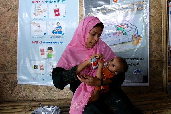 0550-0551  Setara Begum feeds her 7-month-old son therapeutic food provided by the OTP center for children with Severe Acute Malnutrition at Unchiprang makeshift settlement for Rohingya refugees in Teknaf, Cox's Bazar, Bangladesh.      Date-02-01-2018  Photo: UNICEF / b.a.sujaN/Map
