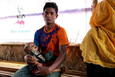 0562-0563  A Rohingya refugee father waits with his son in the waiting room of the OTP center for children suffering Severe Acute Malnutrition at Unchiprang makeshift settlement camp in Teknaf, Cox's Bazar, Bangladesh.     Photo: UNICEF/b.a.sujaN/ Map