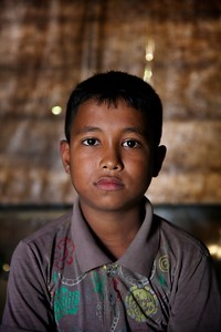0220-0235 Mohammad Zia is a 10-year old child who became an adult overnight. His father was a small business owner. He was killed by the Burmese military while the family was fleeing Rakhine State. Mohammad could not bury his father's body, so he covered it with leaves inside a forest. Mohammad, his mother and his four younger siblings managed to reach Bangladesh. He now collects firewood from a forest near their camp every alternative day for cooking purpose. When he cannot collect firewood, he uses plastic bottles, which are highly toxic. He is registered with a UNICEF-supported learning center, but sometimes he misses attending school as he needs to help his mother. Mohammad wants to go to school and continue to improve his English.  Photo: UNICEF / b.a.sujaN / Map
