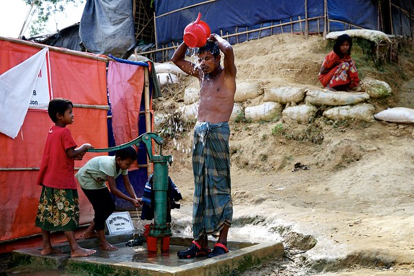 0408-  Seven-year-old 'Aktara' pumps water for her father as he bathes next to a tube well at the Bormapara refugee settlement in Ukhia, Cox's Bazar, Bangladesh.  Date-20-12-2017 Photo: UNICEF/b.a.sujaN/Map
