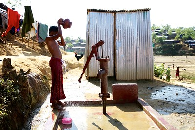 0406-0407  A Rohingya child bathes next to a tube well at the Balukhali makeshift settlement in Ukhia, Cox's Bazar, Bangladesh.  Date- 20-12-2017 Photo: UNICEF/b.a.sujaN/Map