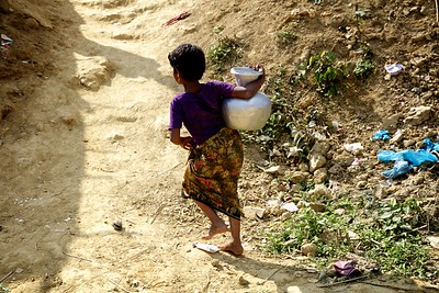 0409-  A Rohingya child walks home with a heavy jar of water.     Date-20-12-2017 Photo: UNICEF/b.a.sujaN/Map