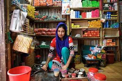 0008-0014 Sonia (18 years old) studying in collage. She is selling Tea, Some times she also look after the shop. Living with parents, 3 brothers & 2 Sisters. She received cash stypen from a partner NGO. With Stypen money she bought a refrigerator for her family shop which is inside the Bhola Bosti(slum). Her parents came to dhaka long time back because of river erosion from Bhola (a island from delta) Bhola Bosti(Slum), pallobi, Mirpur, Dhaka. Bangladesh.  Photo: sujaN/UNICEF/Map www.sujanmap.com