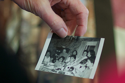 A member of the Class of 1962 holds up a picture of her classmates from when they were still in high school.