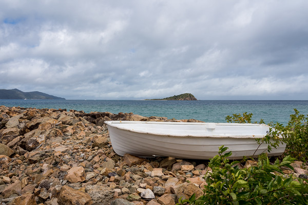MMPI_20200908_MMCK0074_0004 - A dinghy beached on a marina rock wall with ocean and islands as backdrop.