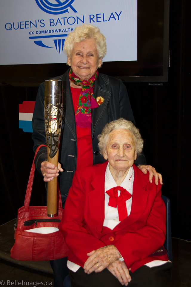 Violet Histed (nee Smith) with sister Trudy Hall (nee Smith) holding the Queen's Baton