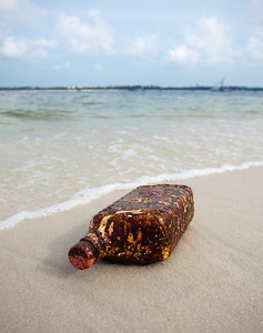 """From the """"Truth Is Stranger Than Fiction"""" category, this quart size oil container, covered in oil, was splashing around in the surf near the Pensacola Pass on 6-13-2010. Oh, sweet irony. Or light sweet crude irony in this case."""