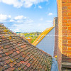 View between roof tops and brick walls to English Landscape. Property Released; Yes.
