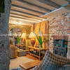 Lounge room rustic support and ceiling beams  brick wall and golden hue lighting reflected in mirror