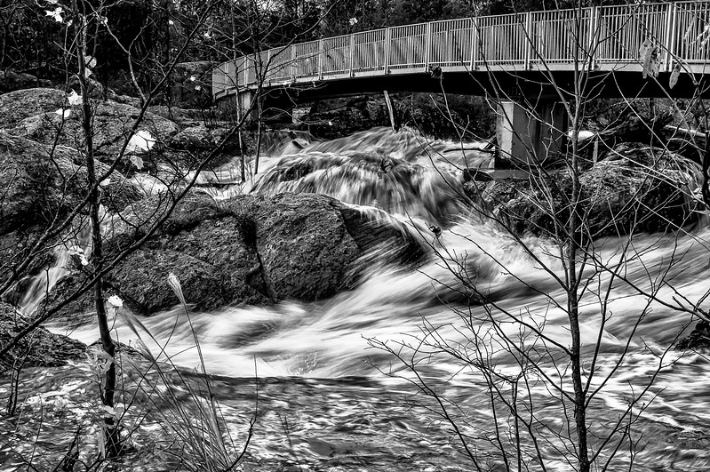 Great Falls MD - Overlook, The Olmsted Trail Bridge as flood waters stream by amongs millenium aged rocks.