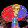 A Night at the County Fair.  A Time-Lapse photo of Powers Great American Midway carnival swing.  The white concentric swirls and shadows are people spinning in the swings.