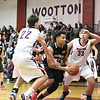 QO's Daniel Dorsey moves down the lane as Wootton defenders Zachary Nannen and Will Quam close in to derfend.