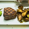 Peruvian Seasoned Filet served with a garnish and broiled braised Brussel Sprouts