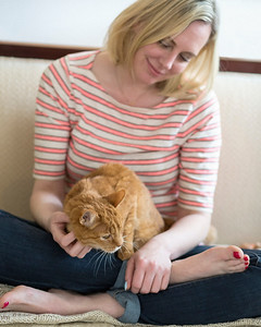 Young woman pets her senior orange tabby cat