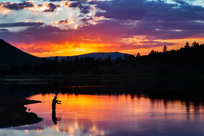 A fly fisherman casting to giant Rainbow trout on Calder lake Utah