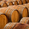 Rows of oak wine barrels in a winery cellar.