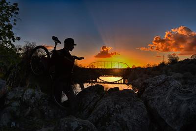 Silhouette of biker and bridge