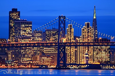 San Francisco city skyline with holiday lights on at night and the Bay Bridge
