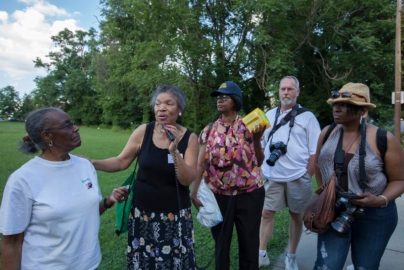 The Society's Urban Photography Series includes guided photo tours of neighborhoods in each of the District's eight wards. The tour of  Brightwood (Ward 4) was led by Pat Tyson. <br /> <br /> PICTURED:  Participants and tour guide along the route. Participants and tour guide along the route. Outside the former Military Road School; tour guide and women in white t-shirt are former students at the Military Road School.<br /> <br /> Shot 6/29/2013. Credit: Anne McDonough, © Historical Society of Washington, D.C.