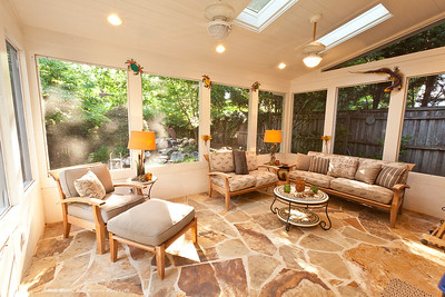 Large, flagstone screen-enclosed outdoor living room overlooks zen garden and pond with waterfall.