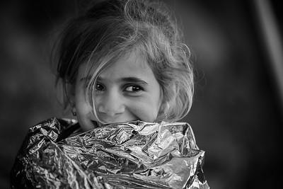 Young refugee resting in an emergency blanket after getting off the boat. Lesvos Island, Greece, 2015 ---- Jeune réfugiée se reposant dans une couverture d'urgence après être débarquée du bateau. Ile de Lesbos, Grèce, 2015