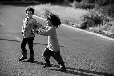 Frère et soeur en marche sur une route qui ne les mènera nul part. Camp d'EKO, Polykastro, Grèce. 2016
