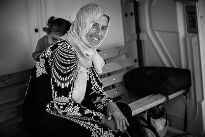 Young girl playing hide and seek from the photographer with her mother. Kara Tepe camp, Lesvos Island, Greece. 2016. ---- Jeune fille jouant à cache-cache avec le photographe dans un camp de réfugiés. camp de Kara Tepe, Ile de Lesbos, Grèce. 2016