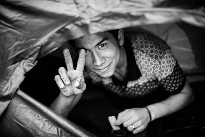 An Afghan man protects himself from the rain in his tent and offers his last cookie to the photographer. Lesvos Island, Greece, 2015 ---- Un homme afghan se protège du déluge sous sa tente et offre son dernier biscuit au photographe  Ile de Lesbos, Grèce, 2015