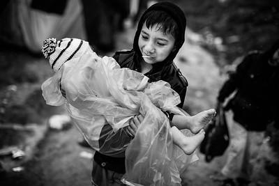 A boy protects his younger brother from the rain in Moria camp. Lesvos Island, Greece, 2015 ---- Un grand frère protège son plus jeune frère de la pluie à travers le camp de Moria. Ile de Lesbos, Grèce, 2015