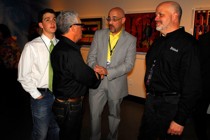 The photographer shaking hands with Rock and Roll Hall of Fame Curatorial Director Howard Kramer, with Toby Pechner and Charlie Randell, CEO of McIntosh Labs, looking on.