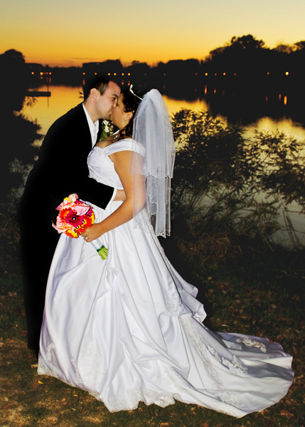 Husband and wife kiss with the sunset beaming on the Fox River in Frame Park.
