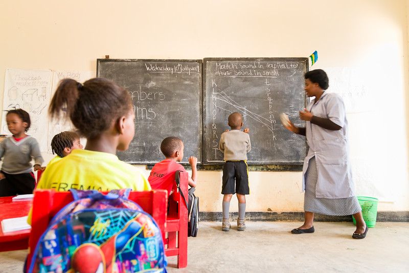 A student writes the answer on a blackboard during an exam in pre-school at a PEACE sponsored school in Kigali Rwanda