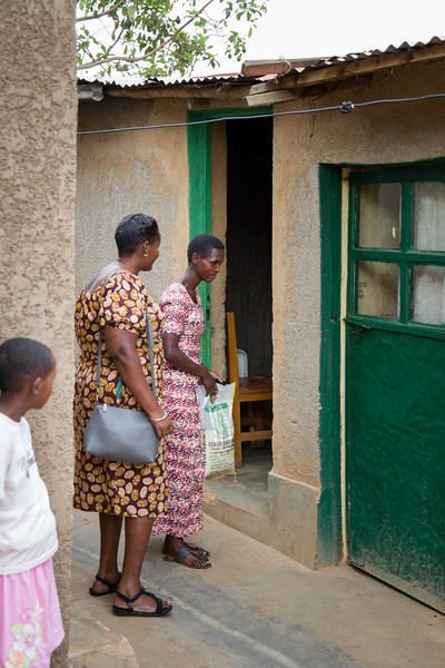 Odethe visits with a widow with HIV and her children.