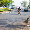 City worker in Kigali Rwanda sweeps the street as traffic passes by.